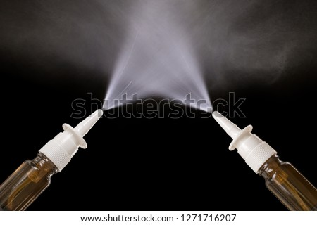 Spraying nasal sprays in front of black background with copy space #1271716207