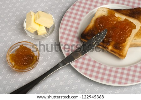 Spread jam on bread with knife