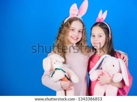 Spread joy and happiness around. Hope love and joyful living. Friends little girls with bunny ears celebrate Easter. Children with bunny toys on blue background. Sisters smiling cute bunny costumes. #1343386853