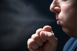 Spread of pathogens when coughing shown with a man against a black background