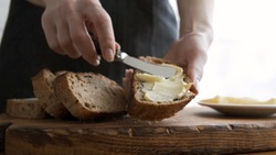 Spreading butter on sourdough bread. Female hand holding piece of bread and smearing organic butter on it