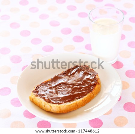 spreading chocolate cream on a slice of bread