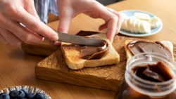 Spreading chocolate nut butter on toasted bread. Female hands smear chocolate spread on sandwich bread. Preparing lunch or breakfast