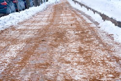 Spreading sand and salt on pavement to increase friction of icy road surfaces in winter season, and prevent pedestrian injury. Snowy road covered with sand