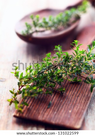 Sprig of fresh thyme lying on a rustic wooden chopping board in a country kitchen to be used as a seasoning in cooking