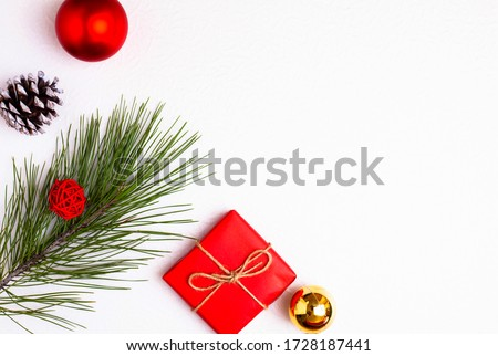sprig of spruce, red gift, Christmas tree toy and bump. minimalism.Copy space