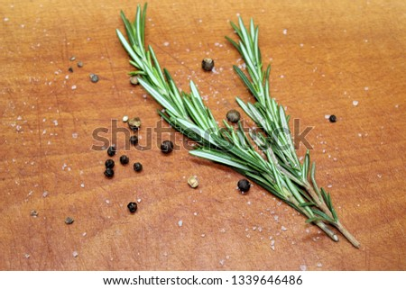 Sprigs of rosemary, laid on a cutting wooden board with black and allspice peas #1339646486