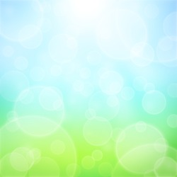 Spring abstract background with bokeh and sun rays. Grass and blue sky