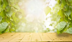 Spring and summer background - fresh green birch leaves, frame in the rays of sunlight, with a wooden table. Abstract natural backgrounds to showcase and promote your product.