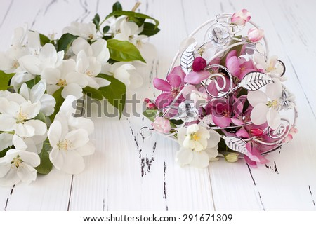 Spring apple tree blossoms and vintage cage heart on white old wooden background. Wedding or valentine concept