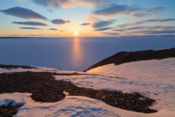 Spring arctic landscape with the midnight sun and the coast of the Arctic Ocean. North of the Arctic Circle at the end of May, the sun does not set at night over the horizon. Pevek, Chukotka, Russia.