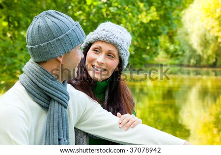 Spring autumn smiling couple sitting on a park sea being happy in the late summer with cold weather