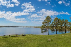 Spring background landscape. Blue sky with white Cirrus clouds, clear lake Ferapontovskoe, Russia, trees grow on the shore of the lake, a bench is installed for tourists to relax.