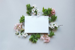 Spring background with paper sheet. Beautiful fresh flowers and leaves on gray background.