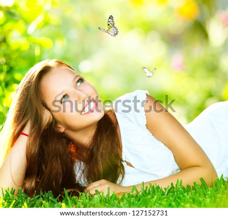 Spring Beauty Girl. Beautiful Young Woman Lying on Green Grass outdoor. Park. Meadow. Summer. Spring Girl lying on the Field. Happiness. Outdoors. Youth concept