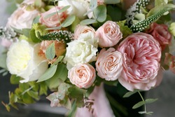 Spring bouquet of mixed flowers on vintage gray wall background behind