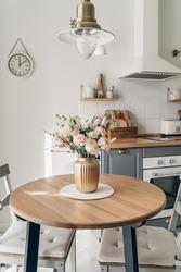 Spring bouquet on wooden table in the kitchen.  Scandinavian style. White wooden background. Bright kitchen interior