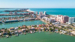 Spring break or Summer vacations in Florida. Ocean beach and Resorts in US. Blue-turquoise color water. American Coast or shore. Island in Gulf of Mexico. Clearwater Beach FL. Aerial view of city.
