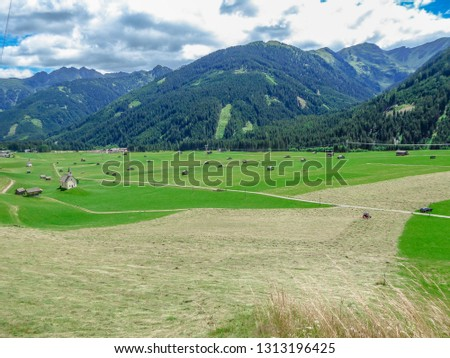 Spring came to the Alpine valley, turning the meadow into lush green color. Lots of small cottages and agricultural machinery on the grassland. High Alpine peeks around the valley. Small church.