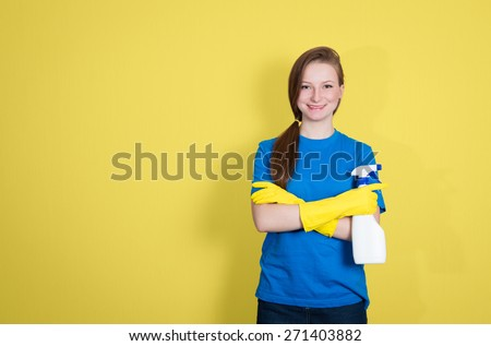 Spring cleaning. Cleaning woman with cleaning spray bottle happy and smiling. Beautiful cleaning girl isolated on yellow background with copyspace.