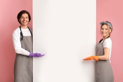 Spring Cleaning Sale. Positive couple wearing gloves and aprons and pointing at blank white advertising board with open palms, recommending something