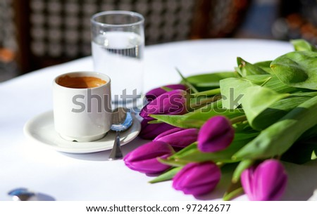 Spring coffee. Cup of fresh espresso and bunch of beautiful tulips