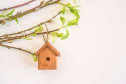 Spring concept with little birdhouse and young willow twigs with leaves on white background and copy space
