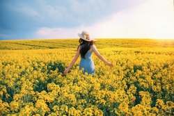 spring day. happy woman turned away back, walks run along yellow field rapeseed, hands raised to side enjoys nature blue sky. Girl brunette long black hair fly in wind. Jeans sundress straw hat flower