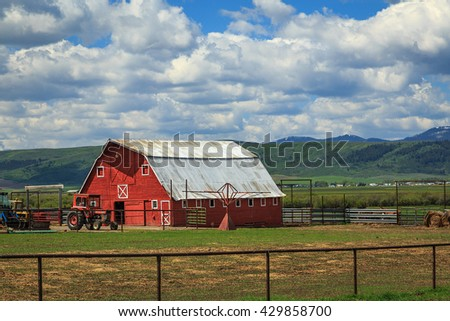 Spring day with a red barn in rural Wyoming, USA.