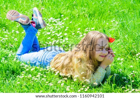 Spring delight picture of little girl laying in grass holding red tulip posing for camera. Child enjoy spring while lying at meadow. Spring mood concept. Girl on smiling face holds red tulip flower.