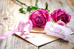 Spring design with peony flower and Mother's Day greeting card wooden background
