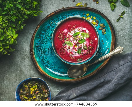 Spring detox beetroot soup with mint, chia, flax and pumpkin seeds on bright blue ceramic plate over grey concrete background, top view. Dieting, clean eating, weight loss, vegetarian food concept