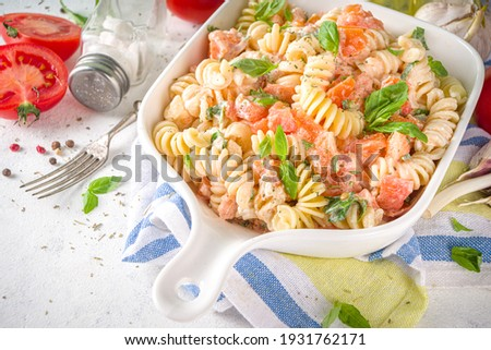 Spring diet healthy vegan pasta. Italian fusilli pasta with tomatoes, green vegetables, fresh herbs, cream cheese or feta, on white table background copy space Foto stock ©