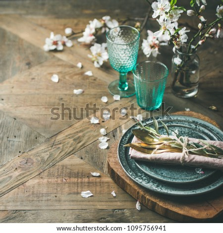 Spring Easter holiday Table setting. Tender almond blossom flowers on branches, plates, glasses and cutlery over vintage wooden table, selective focus, copy space, square crop