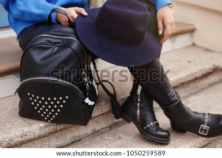 Spring fall outfit fashion details, young stylish woman wearing oversized blue sweater, black jeans and black leather footwear. urban fashion blogger posing with a black trendy handbag. autumn fashion #1050259589