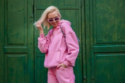 Spring fashion concept: happy smiling fashionable woman wearing trendy pink sport chic style outfit posing in street on green background. Sunglasses, pink hoodie, trousers. Copy, empty space for text