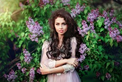 Spring fashion girl outdoors portrait in blooming trees.Beauty romantic woman in flowers of lilac.Sensual lady with long dark shiny hair. Beautiful girl in lacy dress looking at camera. Warm photo.