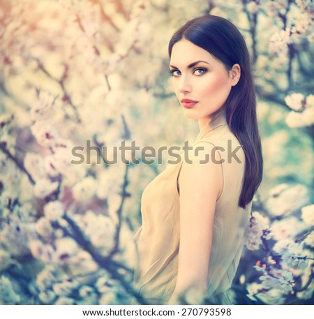 Spring fashion girl outdoors portrait in blooming trees. Beauty Romantic woman in flowers. Sensual Lady. Beautiful Woman Enjoying Nature. Romantic beauty in fantasy orchard
