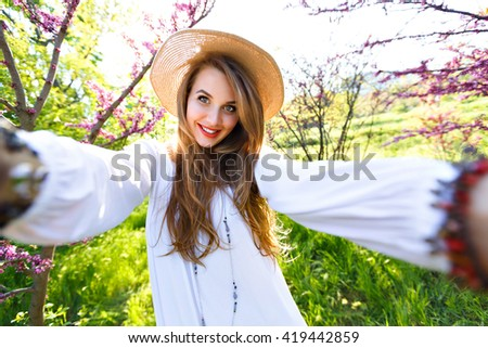 Spring fashion portrait of sensual beauty woman, long hairs pastel make up, posing at blossom garden park, sunny hot day, white vintage dress, trendy accessory . Making selfie, amazing smile, positive