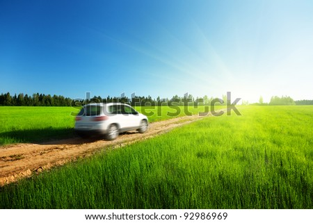 spring field and blured car on ground road - stock photo