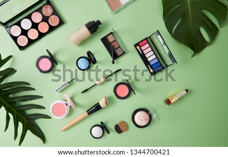 Spring Flat lay composition with skin foundation, powder and beauty accessories, Cosmetic beauty products arranged on a paper green pastel background, Organic cosmetic concept #1344700421