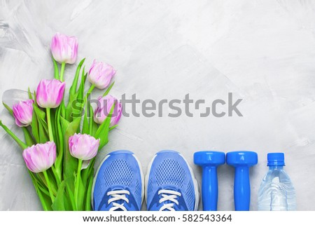 Spring flatlay sports composition with blue sneakers, dumbbells, bottle  of water and purple tulips on gray concrete background. Concept healthy  lifestyle, sport and diet in spring. Top view. #582543364