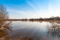 spring flood the river overflowed its banks and overflowed into the fields, blue sky