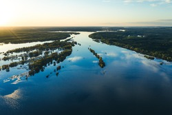 Spring flooding on the river, flooded forest, islands on the river. View from a drone, a bird's-eye view. View without the presence of people in the evening.