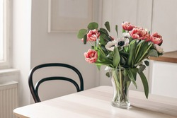 Spring flowers in glass vase on wooden table. Blurred kitchen background with old chair. Bouquet of red tulips, white anemone flowers and eucalyptus branches. Contemporary elegant scandi interior.
