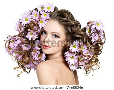 Spring flowers in gorgeous long curly hair of young beautiful woman - white background