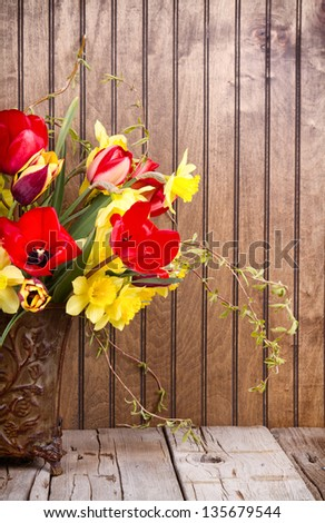 Spring flowers tulips and daffodils in a vase on a wooden background - stock photo