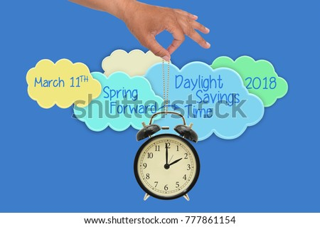 Spring Forward Daylight Savings Time March 11 2018 Clouds Hand dangling 2 o'clock alarm clock blue background