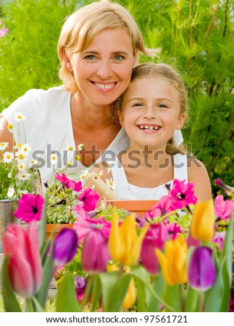 Spring garden, planting concept - mother and daughter working in flowers garden - stock photo