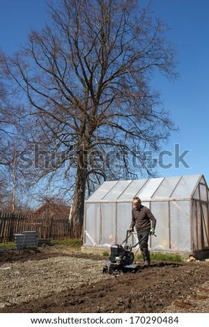 Spring Garden work. man working with Garden Tiller - stock photo